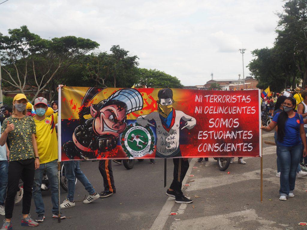 """Nina Lendal (i midten forrest) på La Loma de la Cruz (Korsbakken red.) som nu er blevet omdøbt til Loma de La Dignidad (Værdighedens Bakke). På banneret til venstre står der,""""Må den forfærdelige nat stoppe""""."""