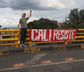 """Nina Lendal foran et banner i Cali, hvor der står, """"Cali gør modstand"""""""
